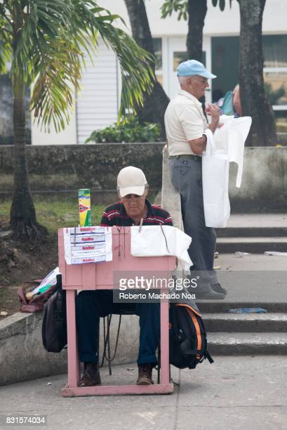 Seniors with private small business Old man sitting on chair behind pink table refilling lighters Another man selling plastic bags
