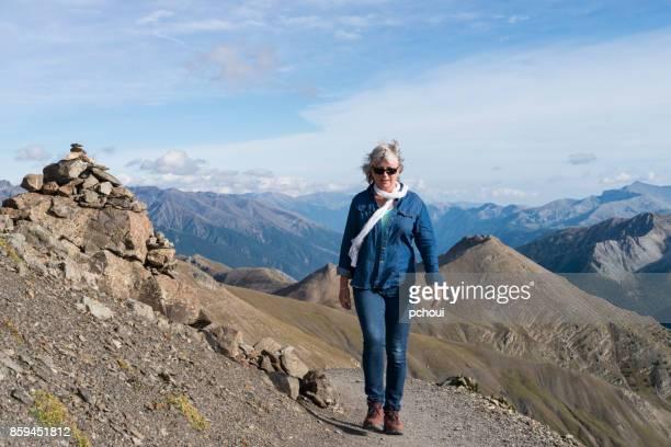 Seniors, woman walking on top of mountain, hiking alps