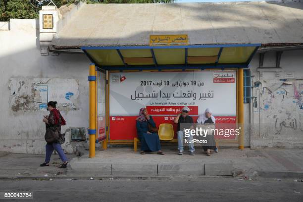A sensitization poster for registration in the Tunisian municipal elections set for December 17 is seen in a bus stop located behind the building of...