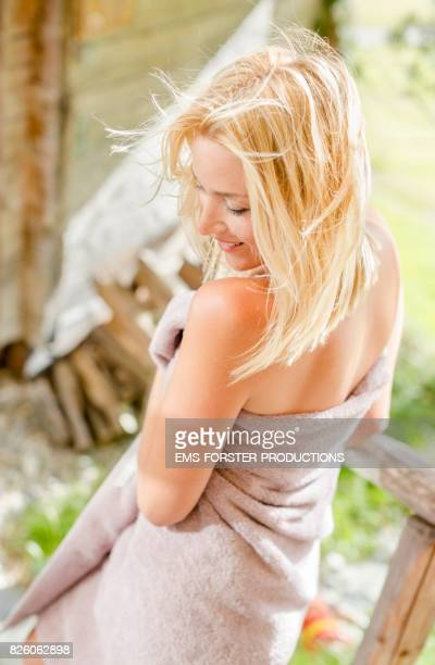 sensual, blonde woman in her 30s with blonde hair wearing a towel only walking down on wooden handrail