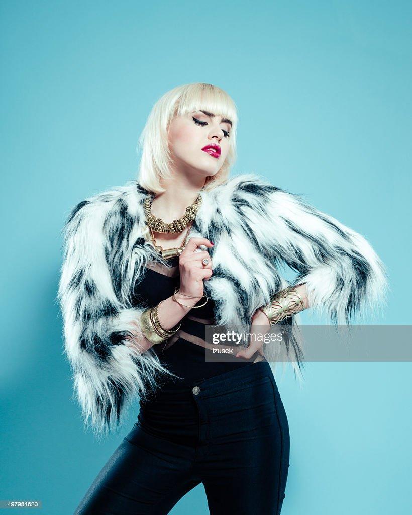 Sensual blonde woman wearing fur jacket and gold jewlery