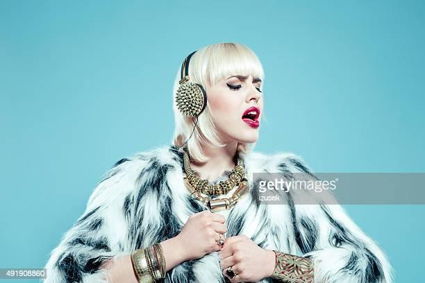Sensual blonde woman wearing fur jacket, gold jewlery and headphone
