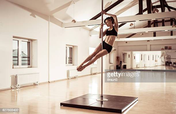 Sensual female dancer dancing on a pole in a studio.