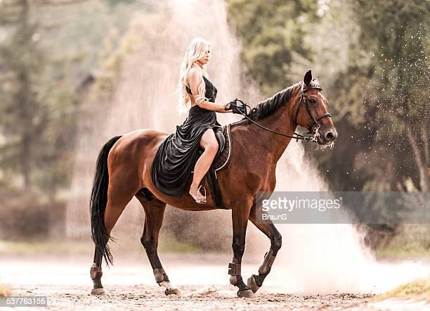 Sensual female fashion model horseback riding.