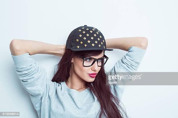Sensual long hair brunette wearing nerd glasses and baseball cap