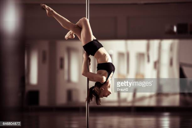 Sensual pole dancer dancing in a studio.