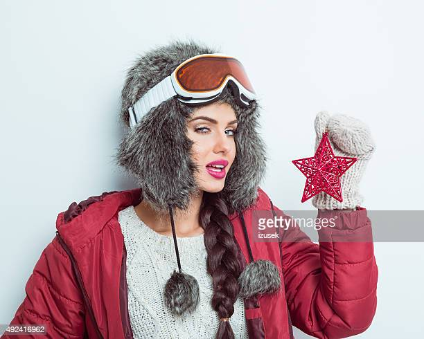 Sensual woman in winter outfit, wearing fur cap and goggle