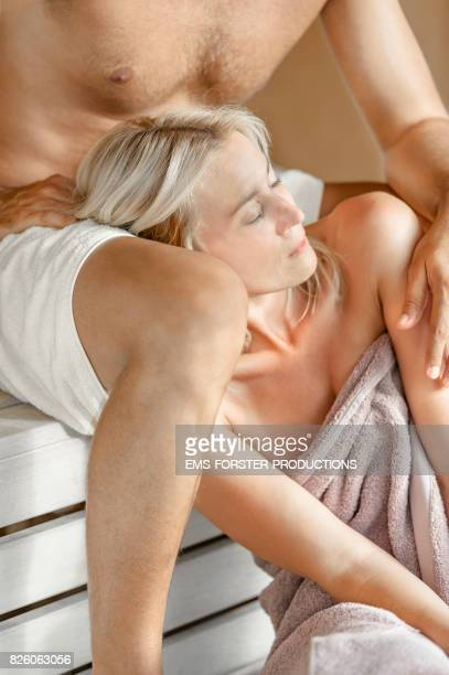 sensual woman is leaning against her man in a wooden sauna while enjoying her parents day and day spa far away from daily routine