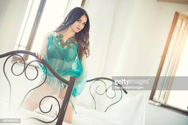 Sensuelle femme posant sur draps dans la matinée