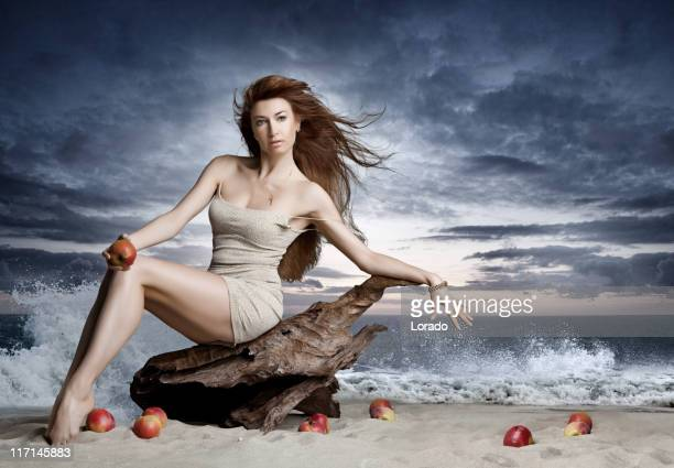 sensual woman sitting on old wood at the beach
