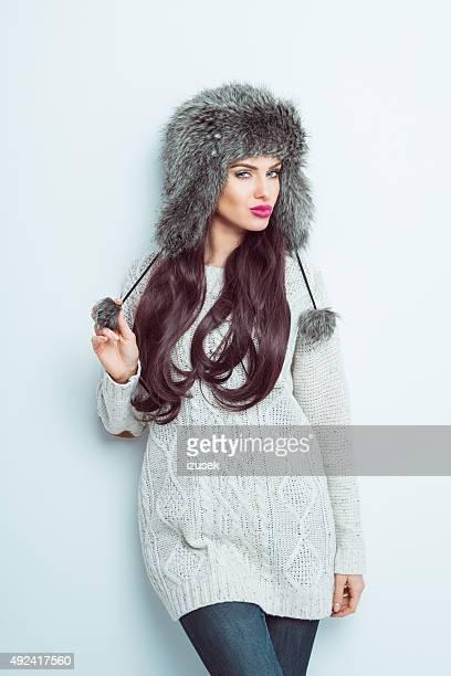 Sensual woman wearing a fur cap sand sweater