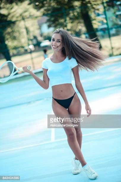 Sensual Young Female Walking in Bikini on Tennis Court