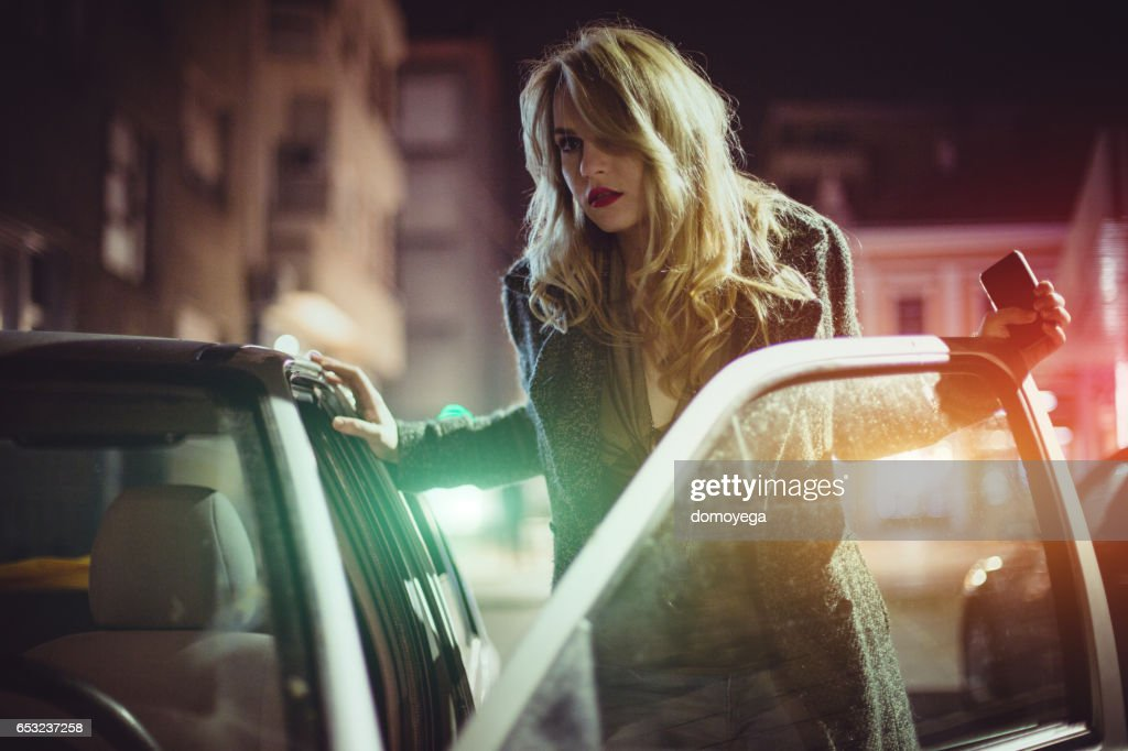 Sensual young woman getting into car : Stock Photo