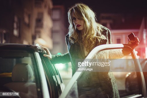 Sensual young woman getting into car : Photo