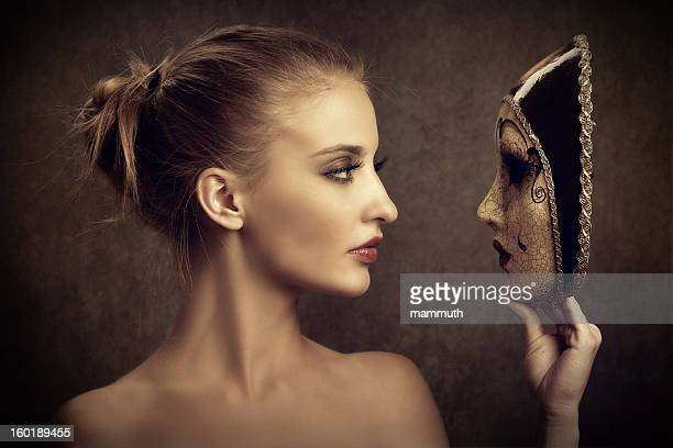 Sensual young woman looking at a venetian mask
