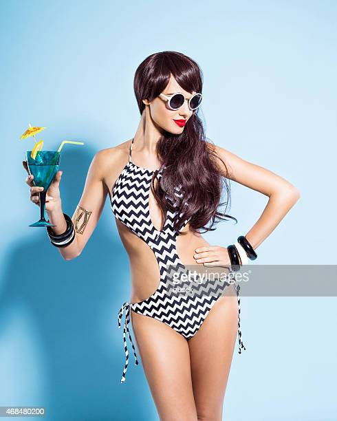 Sensual young woman wearing swimsuit holding drink