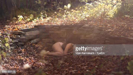 Sensuous Woman Sleeping On Leaves At Forest During Sunny Day