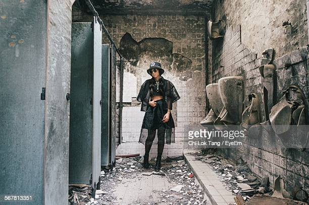 Sensuous Woman Standing In Abandoned Public Toilet