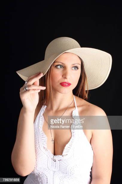 Sensuous Woman Wearing Sun Hat Standing Against Black Background