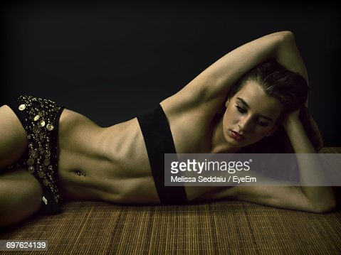 Sensuous Young Woman Lying On Mat Against Black Background