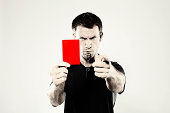 A male, Caucasian sports referee showing a red penalty card and blowing a whistle. Shot in the studio against a light background and with a retro photoshop effect.