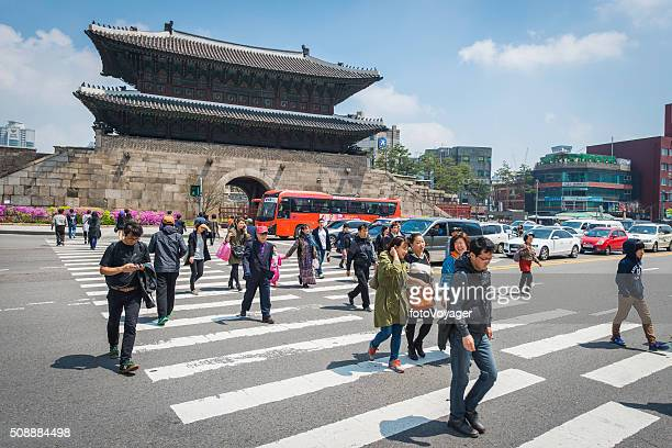 Seoul pedestrians crossing through traffic Heunginjimun Dongdaemun Gate South Korea