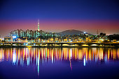 Seoul skyline, looking towards Itaewon at night from Han River with reflections in the water. Highly saturated colors.
