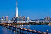 Jamsil bridge over Han River against Seoul Skyline at the blue hour. In the back is the Lotte Tower, the tallest building in Republic of Korea