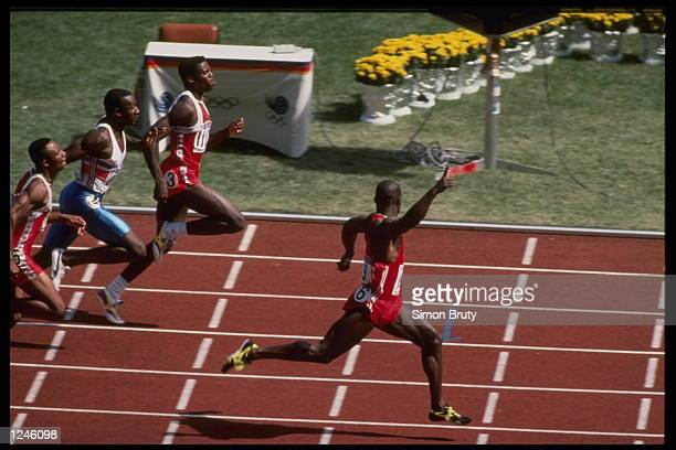 Ben Johnson of Canada celebrates as he crosses the finish line well ahead of Carl Lewis of the USA and Linford Christie of Great Britain to win the...