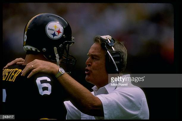 Quarterback Bubby Brister of the Pittsburgh Steelers talks to his head coach Chuck Noll during a game against the Dallas Cowboys at Three Rivers...
