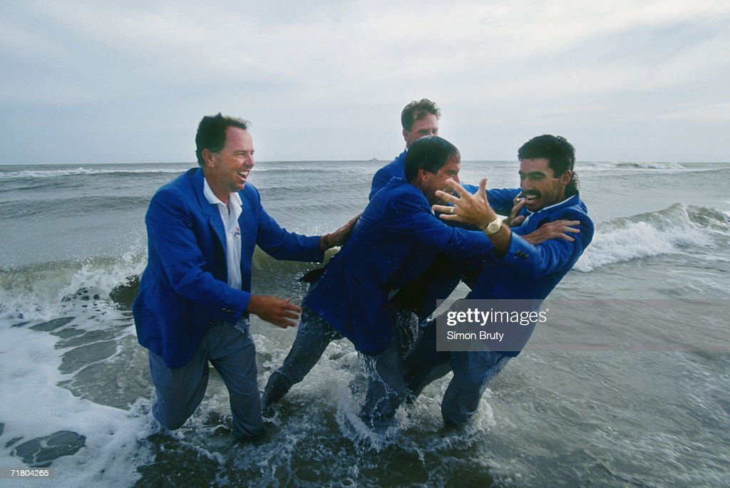 Mark O''Meara and Payne Stewart look on as team captain Dave Stockton pushes Corey Pavin into the water as the USA celebrate on the beach after...