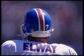 Quarterback John Elway of the Denver Broncos stands on the field of Jack Murphy Stadium in San Diego California where his team clashes with AFC rival...