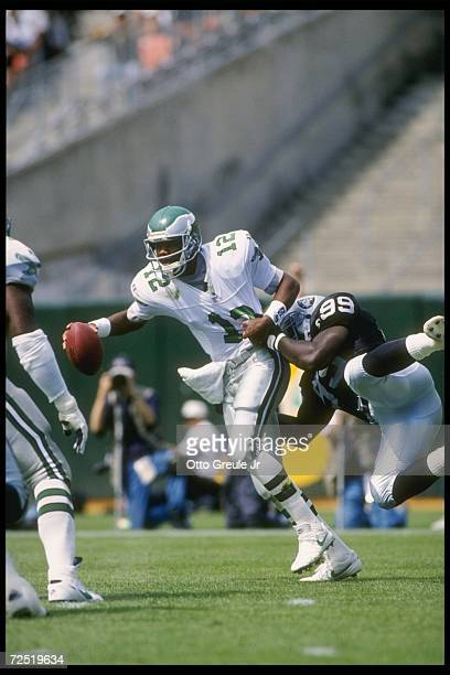 Quarterback Randall Cunningham of the Philadelphia Eagles avoids the reach of defensive lineman Aundrey Bruce of the Oakland Raiders during a game...