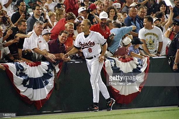 Shortstop Cal Ripken of the Baltimore Orioles runs past fans at Camden Yards in Baltimore Maryland acknowledging congratulations for breaking Lou...