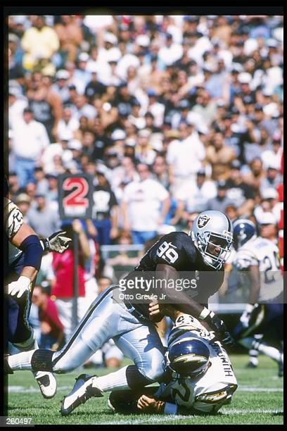 Defensive lineman Aundray Bruce of the Oakland Raiders tackles San Diego Chargers quarterback Stan Humphries during a game at the OaklandAlameda...