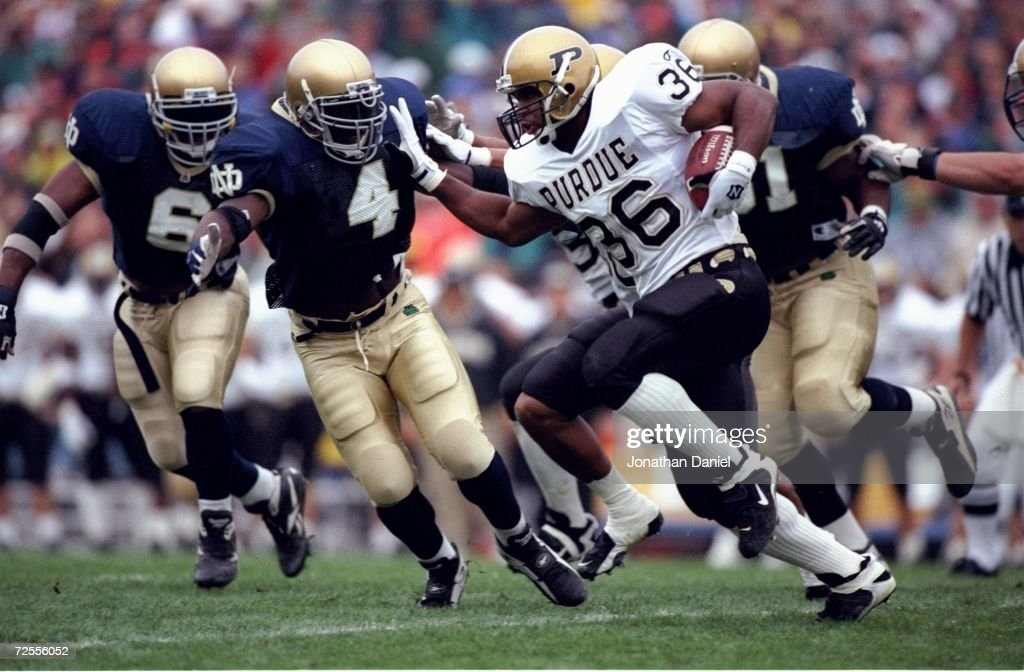Running back Edwin Watson of the Purdue Boilermakers looks up field as he uses his right arm to fend off pursuing defender Kory Minor of the Notre...