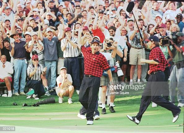 US team members Fred Couples and Davis Love III visibly react in celebration following Couples winning birdie putt on the 17th holed during the final...