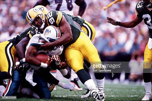 Defensive lineman Reggie White of the Green Bay Packers helps tackle running back Karim AbdulJabbar of the Miami Dolphins durng the Packers 2318...