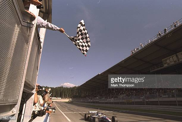Jacques Villeneuve of Canada races past the chequered flag in his Williams Renault to win the Austrian Grand Prix at the A1 Ring circuit in Spielberg...