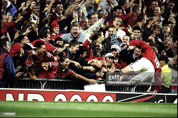 Dwight Yorke of Manchester United is engulfed by adoring fans and joined by team mate Paul Scholes after scoring his first goal for the club during...