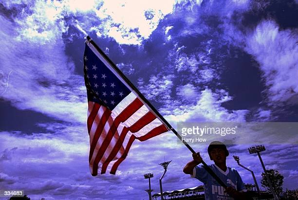Japanese Boy waves the American Flag during the ISF Women''s World Championships game of Team Japan against Team Australia at the Yamamiya Sports...