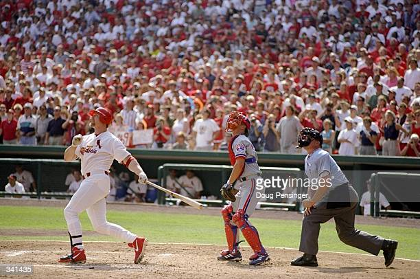 Mark McGwire of the St Louis Cardinals hits his 70th home run of the season as catcher Michael Barrett of the Montreal Expos and umpire Rich Rieker...