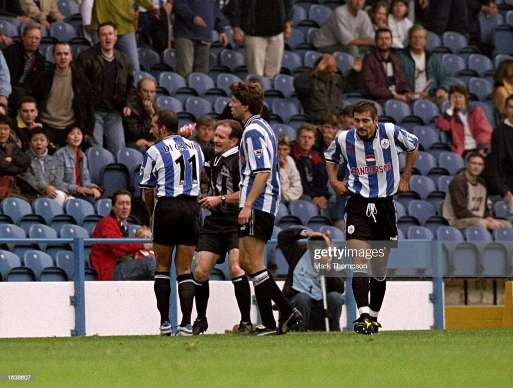Paolo Di Canio of Sheffield Wednesday confronts referee Paul Alcock during the FA Carling Premiership match against Arsenal at Hillsborough in...