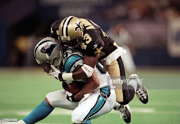 Ashley Ambrose of the New Orleans Saints tackles Rae Carruth of the Carolina Panthers at the Louisiana Superdome in New Orleans Louisiana The Saints...