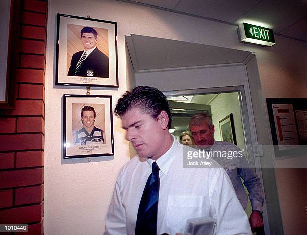 Australian Football League club Geelong coach Gary Ayres walks past the club portraits of himself and 1999 captain Leigh Colbert following his press...