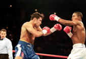 Felix Trinidad throws a left at Oscar De La Hoya as De La Hoya blocks during their welterweight title fight at the Mandalay Bay Casino in Las Vegas...