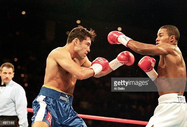 Felix Trinidad throws a left at Oscar De La Hoya as De La Hoya blocks during their welterweight title fight at the Mandalay Bay Casino in Las Vegas...