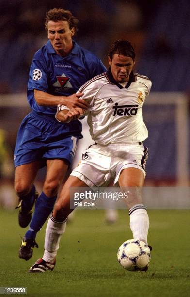 Fernando Redondo of Real Madrid is tackled by Odd Inge Olsen of Molde during the Champions League match played at the Bernabeu Stadium in Madrid...
