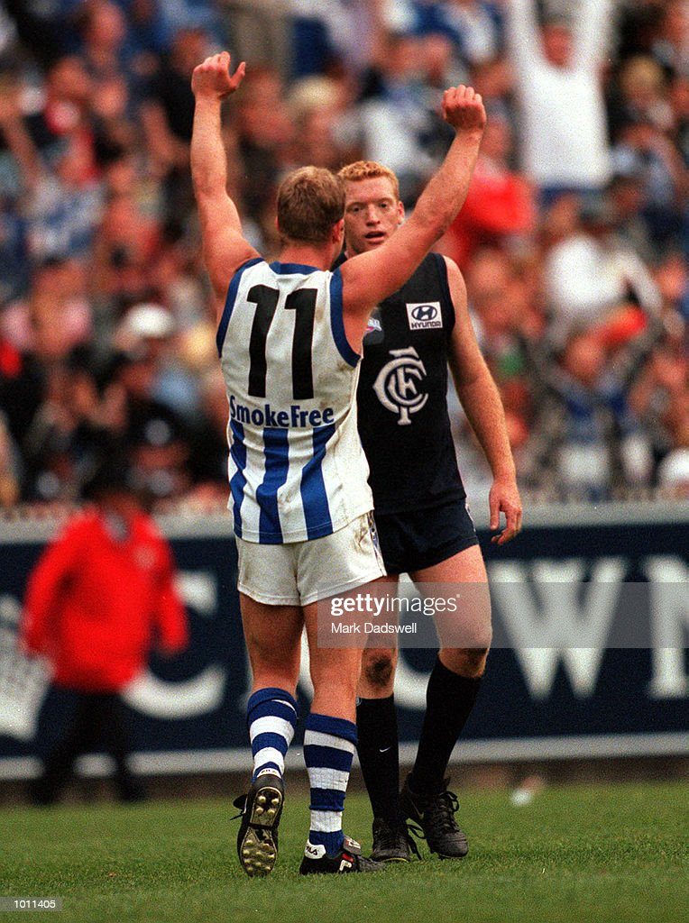 Glenn Archer #11 for the Kangaroos celebrates as Lance Whitnall #8 for Carlton looks on, in the AFL Grand Final match between the Kangaroos and Carlton, played at the Melbourne Cricket Ground, Melbourne, Australia. The Kangaroos defeated Carlton. Mandatory Credit: Mark Dadswell/ALLSPORT