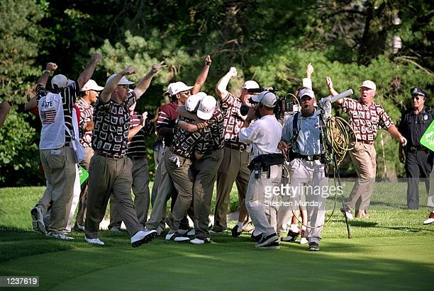 Justin Leonard of the USA is mobbed by the American team after sinking a long birdie putt on the 17th during the final day of the 33rd Ryder Cup at...